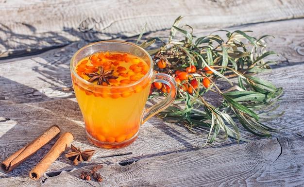 Горячий витаминный чай из облепихи в чашке, стоит на старом деревянном фоне. расслабление и фитотерапия, противопростудные напитки, сезон гриппа