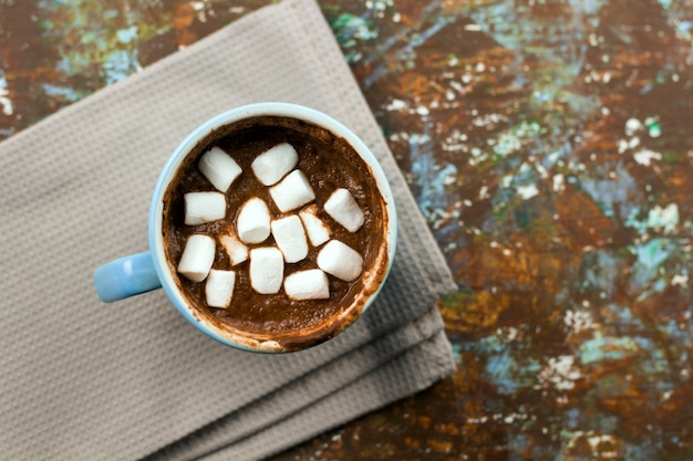 Hot warming chocolate with marshmallows on wooden table served on cloth copy space