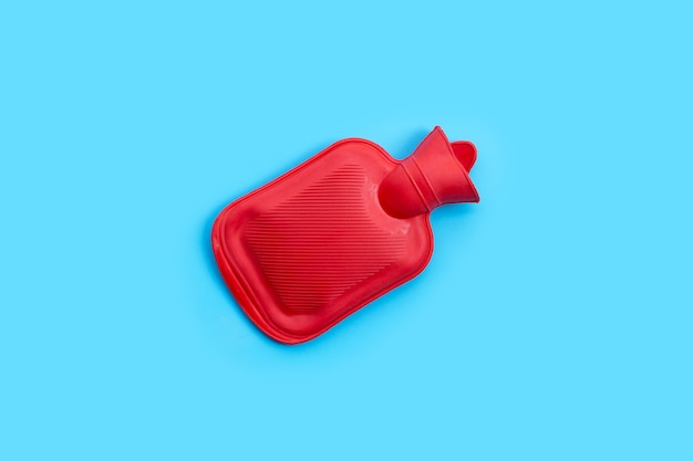 Hot water bag on blue wall. copy space
