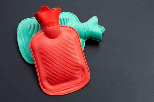 Hot water bags on dark surface. top view