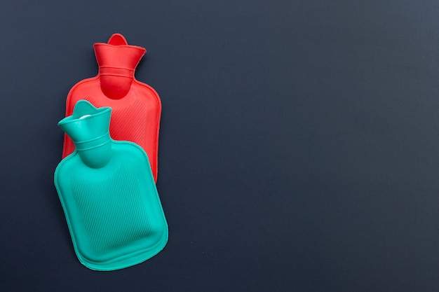 Hot water bags on dark wall. copy space