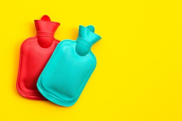 Hot water bags on yellow wall. copy space
