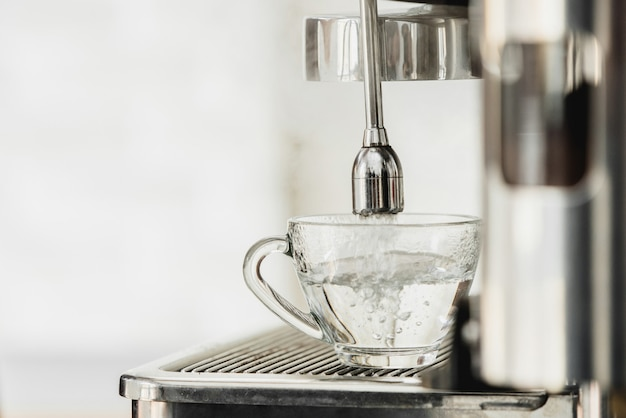Hot water from coffee maker machine flowing into the cup for americano making