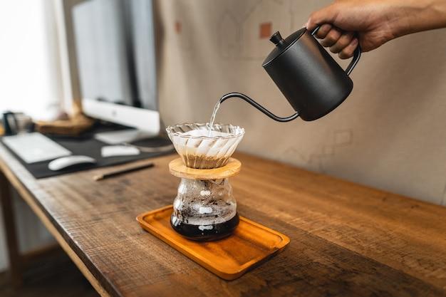 유리병 위의 커피 드리퍼에 뜨거운 물.