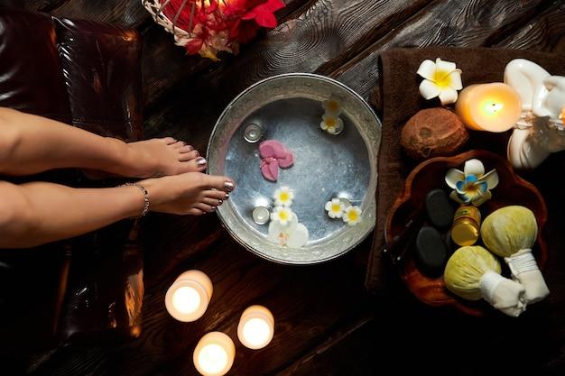 Горячая вода с цветами для распаривания ног, спа-процедуры, свечи и фрукты