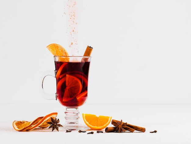 Hot wine on a light background and pouring cinnamon powder