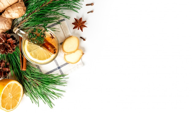 Hot winter aromatic drink. ginger tea with lemon, cinnamon, star anise, cones and green christmas tree branches on a white background, top view, flat lay, copy space.