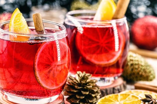 温かい冬の飲み物、温かいクリスマスワイン、シナモンドリンク、ワイン、柑橘類