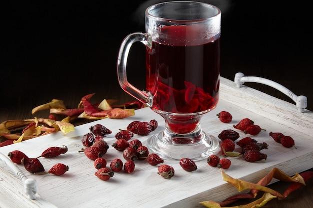 Горячий зимний напиток в окружении сушеных плодов шиповника и яблок на выкрашенном в белый цвет деревянном подносе