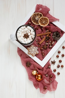 Hot winter drink with marshmallow, gingerbread, spices and christmas decor