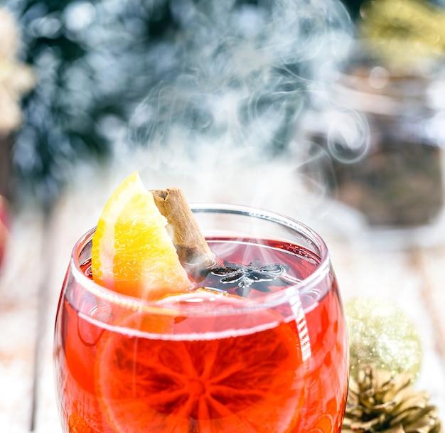 熱い冬の飲み物、煙と蒸気、熱いクリスマスワイン、シナモンと一緒に飲む