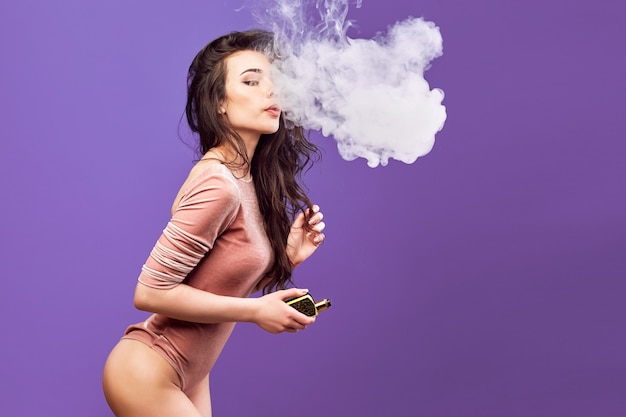 Горячая женщина в боди стоя и вейпинг на фиолетовой стене.
