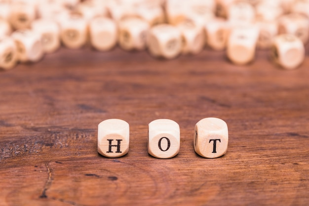 Hot word arranged in row over wooden desk