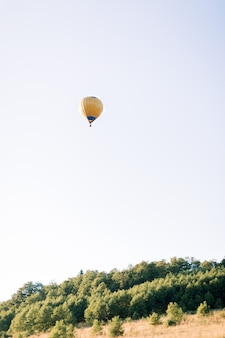 Hot yellow air balloon high in the sky, flying in beautiful green summer field at sunset