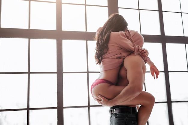熱い若いカップルが窓際に立ち、セーターの下に頭を隠します