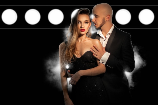 Горячая молодая стильная влюбленная пара носит задние костюмы и позирует в студии на темной стене с дымом