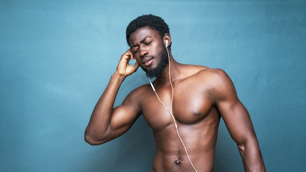 Giovane uomo africano in topless caldo che ascolta musica con gli auricolari su un blu