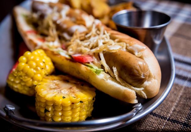 皿にホットドッグとフライドポテト。ファーストフードの食事。飲食店。