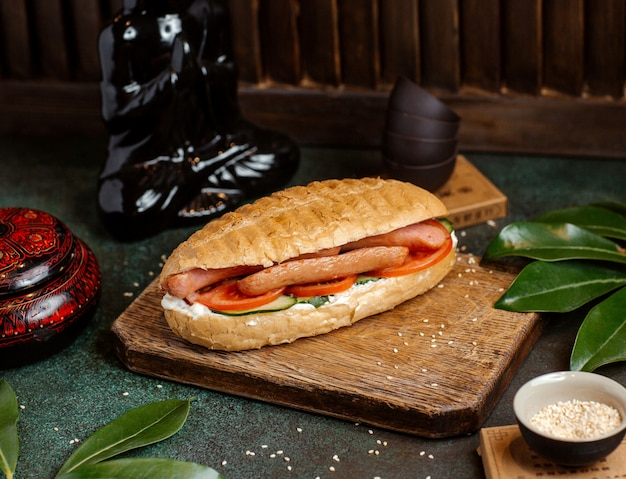Хлеб хотдог, фаршированный колбасками, помидорами, огурцом и майонезом