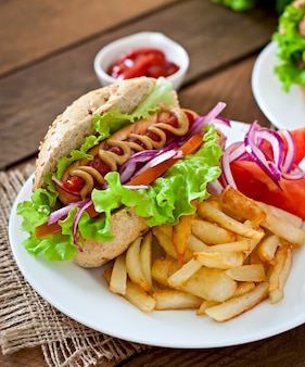 Hotdog with ketchup mustard and lettuce on wooden table.