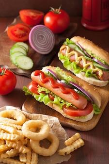 Хот-дог с кетчупом, горчицей, овощами и картофелем фри