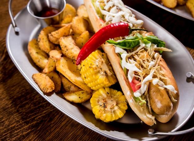 Хот-доги и картофель фри на блюдах. фаст фуд еда. ресторан.