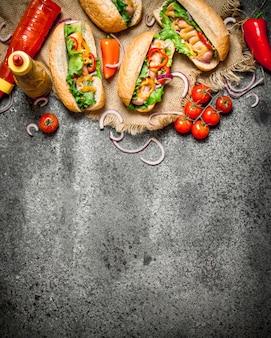 Хот-доги с луком, перцем, помидорами и зеленью, заправленные кетчупом и горчицей