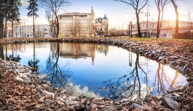 池の水と美しい木々と日光に反射するモスクワのホテルバルチュグ