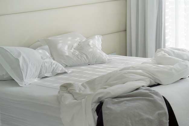 Гостиница кровать после использования. грязная кровать, подушка, одеяло, комната.