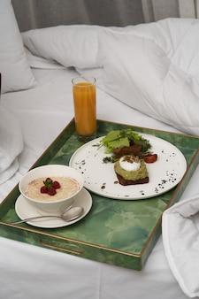 Завтрак в отеле в постель. гостиничный сервис завтрак со свежевыжатым соком, кашей и блинами