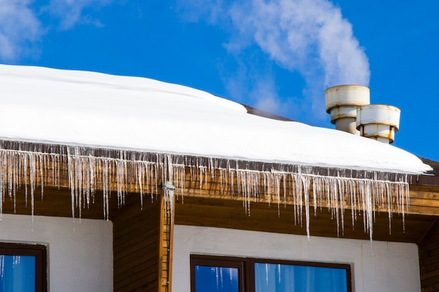 Hotel exterior in ski resort, snow, sunny day and ice. windows and roof.