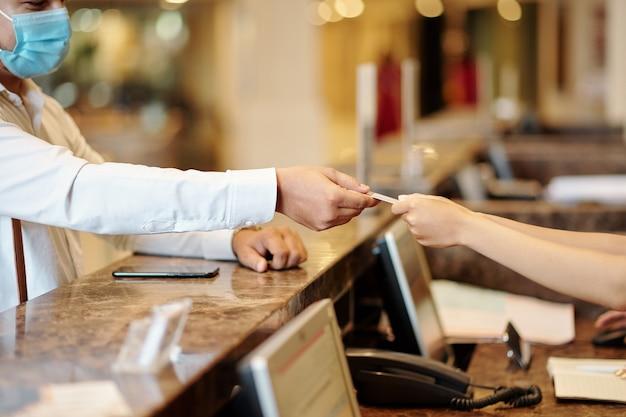 ホテルのゲストがルームサービスの支払いのために受付係にクレジットカードを渡す