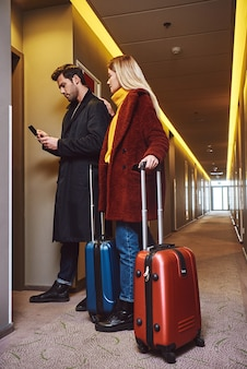In hotel hall. young couple enter to the hotel floor with their luggage and having a chat. full length