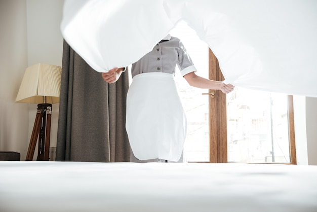 Hotel maid changing bed sheet
