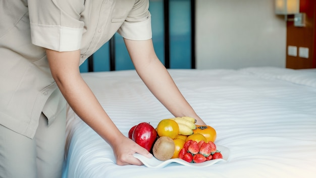Hotel maid hand holding fruits tary  in to the luxury hotel bed room ready for tourist travel.