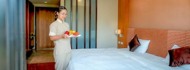 観光旅行の準備ができている高級ホテルのベッドルームに果物を持っているホテルのメイド。