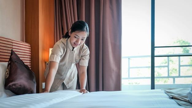 観光旅行の準備ができている高級ホテルの部屋のベッドを作るホテルのメイド。