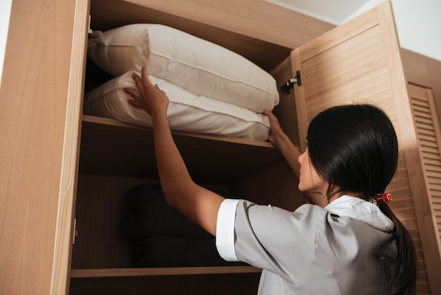 Hotel making putting bed pillows in a cupboard