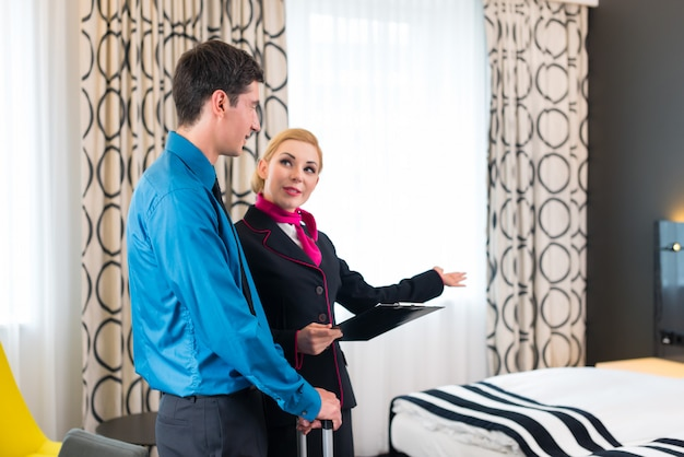 Hotel manager welcoming guest showing room