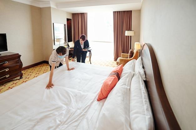 新しいメイドに適切にベッドを作る方法を説明するデジタルタブレットを持ったホテルマネージャー