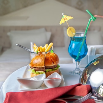 Hotel meal on a table with sandwich, hamburger, cocktails and others side view in bedroom