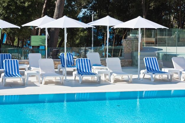 Стулья у бассейна отеля с видом на море. летний выстрел