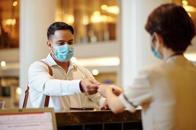 医療マスクでゲストにデジタルルームキーを与えるホテルの受付係