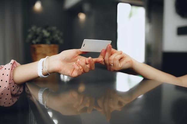 프런트 데스크에서 고객에게 키 카드를주는 호텔 접수 원