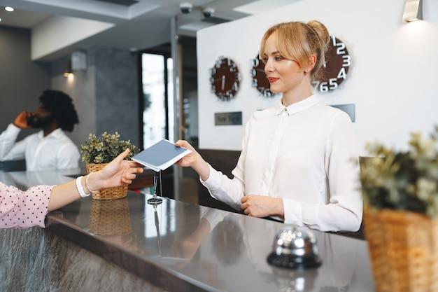 ホテルの受付の女性がチェックのためにゲストのパスポートを取ります