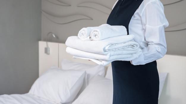 ホテルのルームサービス作成室。折りたたまれた白いバスタオルのスタックを保持し、客室のベッドの横に立っている若い女性の女中