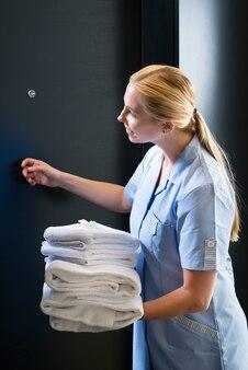 Обслуживание номеров в отеле - молодая горничная стоит перед дверью номера в люксе со свежими полотенцами