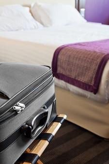Гостиничный номер с чемоданом на багажном отделении и кроватью.