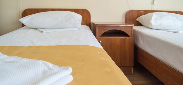 Hotel room with two empty single beds and bedside tables, the concept of the hotel business.