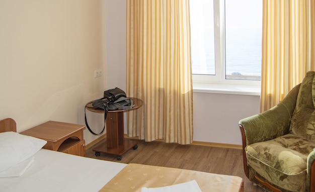 Hotel single room with a bed, an armchair and a table with men's black bags, sea view from the window.